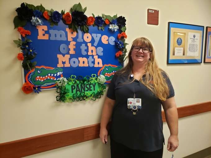 pansy is the urology medical plaza clinic employee of the month.  she is pictured standing in the hallway of the clinic.  she is wearing scrubs.  she is standing by a bulletin board decorated with orange and blue letters they read employee of the month.