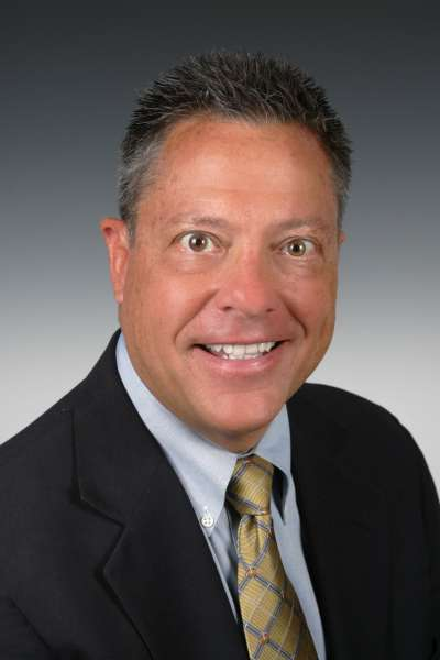 professional photo of doctor krick. he is wearing a dark suit with a light blue collared shirt and a yellow and gray tie.