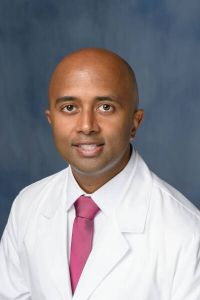PROFESSIONAL PHOTO OF DOCTOR RAMNARAIGN. HE IS WEARING A WHITE DOCTORS COAT WITH A WHITE COLLARED SHIRT AND A PINK TIE.