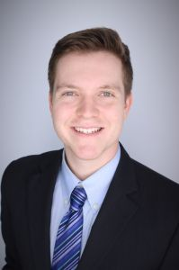 a headshot of medical student bergen lemack.  he is wearing a dark blue suit with a blue collared shirt and dark and light blue striped tie.