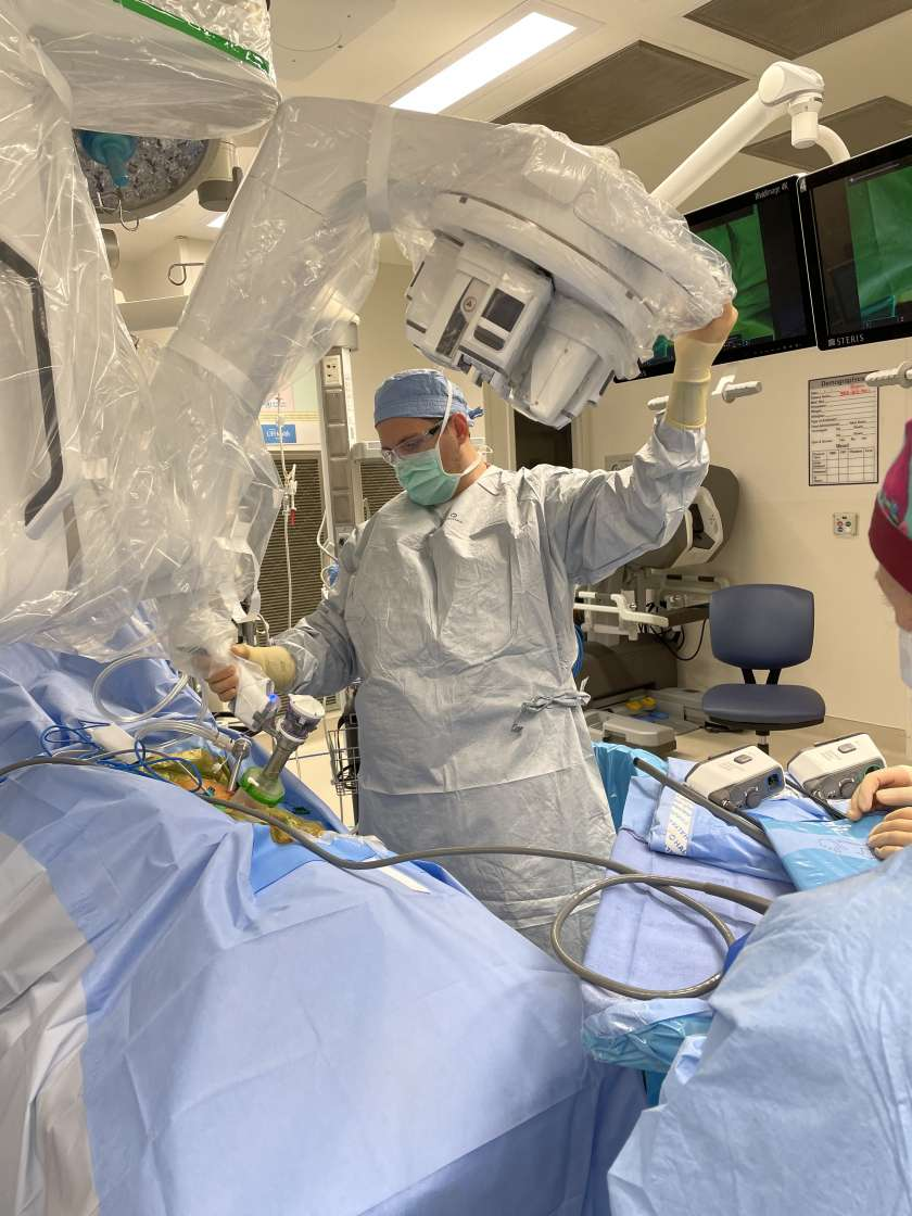 doctor archer dressed in scrubs, scrub hat and mask is in the operating room. he is positions the robotic machine getting ready for a procedure.