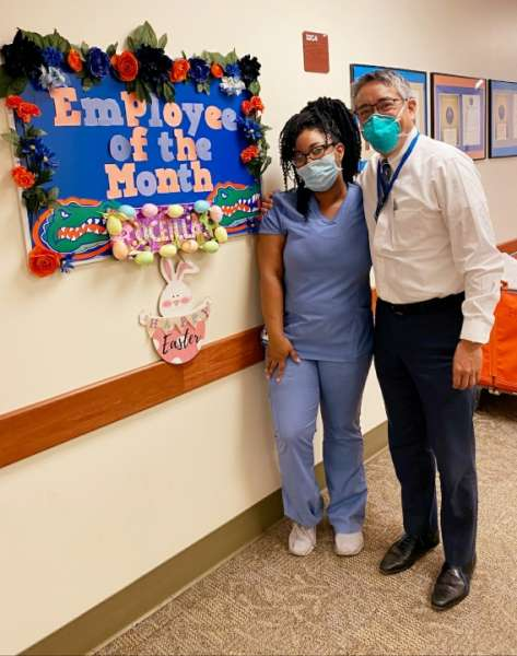 pictured are clinic employee oceilla oats and urology chairman li-ming su.  oceilla is wearig blue scrubs and doctor su is wearing dress pants, dress shirt and tie.  the are standing in front of a bulletin board that reads employee of the month.  it is decorated in orange and blue.  they are both wearing masks.