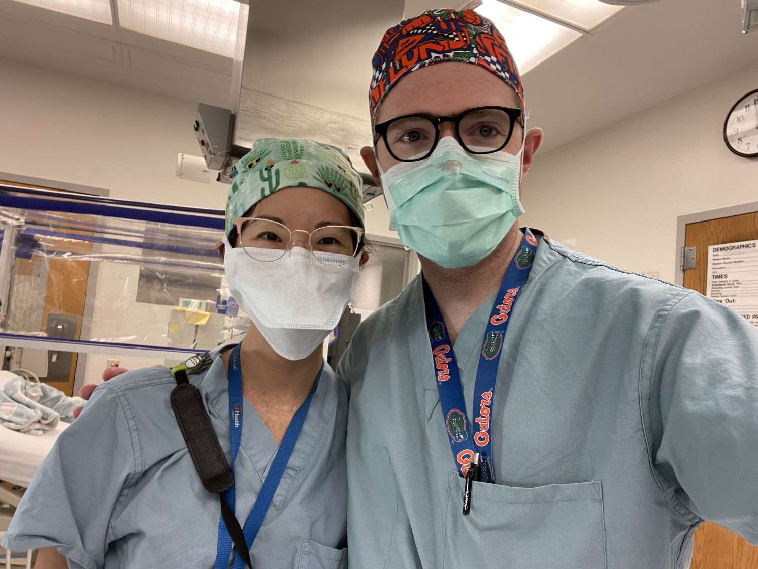 doctors kuo and bayne. both dressed in scrubs, scrub hats and masks. they are in the practice lab.