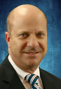 Professional headshot of doctor gary lemack. he is wearing a black suit jacket, a white collared shirt with a blue, cream and gold stripped tie. the background of the photo is blue.