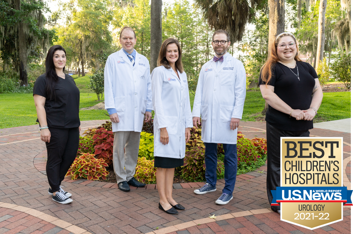 a group photo. the uf health urology pediatric team is pictured. emily wolf dressed is black scrubs is on the far left. Next to her is doctor demarco dressed in a white doctors coat, blue collared shirt and blue multi colored tie. He has on khaki pants. Next is Lindsay rohan dressed in a black dress with white doctors coat. Doctor chris bayne is next to her dressed in a white doctors coat, white collared shirt and orange and blue bow tie. On the far right next to doctor bayne is amber stanle. She is dressed in black scrubs.  In the bottom right corner is the us news and world report best children's hospital banner.