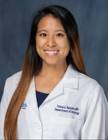 doctor Trisha Nguyen is in her doctors white coat. she has on a blue shirt.