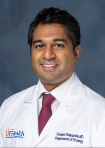 doctor chaparala is wearing a white doctors coat.  he has on a white collared shirt and a red tie.