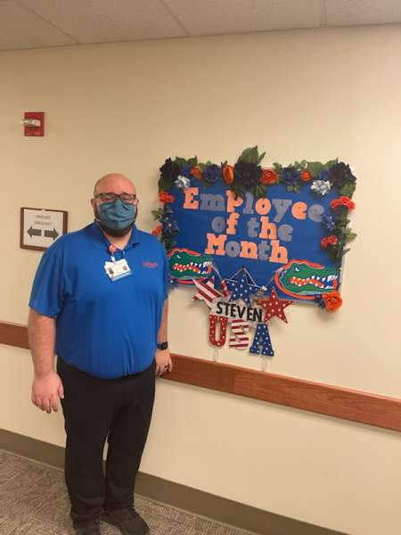 STEVEN WESTBERRY,THE UF HEALTH UROLOGY CLINIC EMPLOYEE OF THE MONTH. HE IS STANDING IN THE HALLWAY OF THE CLINIC. HE IS WEARING BLACK PANTS AND GATOR BLUE POLO SHIRT. HE IS STANDING NEAR THE EMPLOYEE OF THE MONTH BULLETIN BOARD THAT IS DECORATED IN GATOR COLORS AS WELL AS RED WHITE AND BLUE