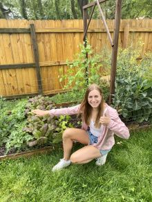 Miranda in her backyard garden.  she is posing near some of her plants.  she is wearing shorts, t shirt and jacket.