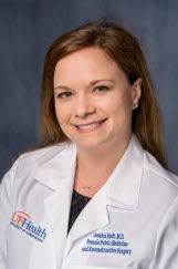 a headshot of doctor heft. she is wearing a white doctors coat and a dark top