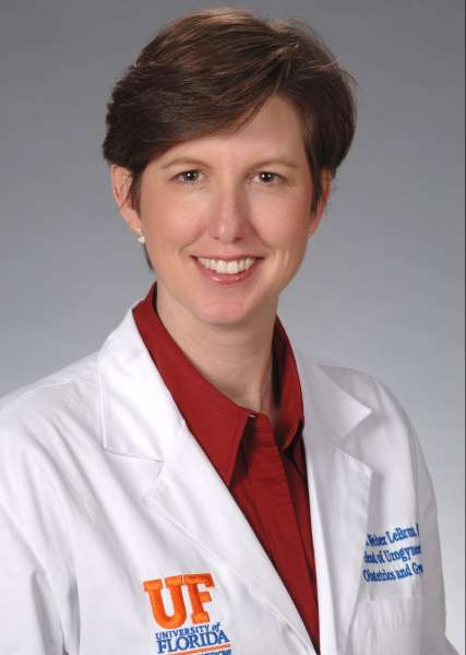 a headshot of doctor lebrun  she is wearing a white doctors coat with a red top.