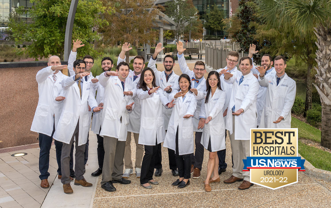 This is a group photo consisting of Department of Urology Residents. They are standing in two rows. They all are wearing a white lab coats. The residents are doing the gator chomp. The background is of a tan walkway made of small pebbles. There are also green trees and a silver metal fence.