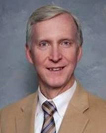 professional photo of doctor robert donnell. he is wearing a tan jacket, white collared shirt and brown striped tie